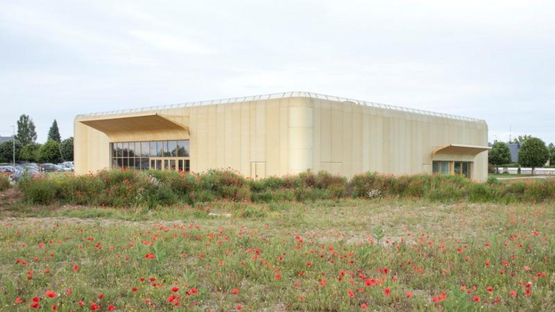 Salle multigénérationnelle, signée CoCo, dans un contexte urbain épars